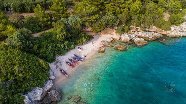 Aerial view of group of kayakers resting on a secluded beach near Drvenik in Dalmatia, Croatia.