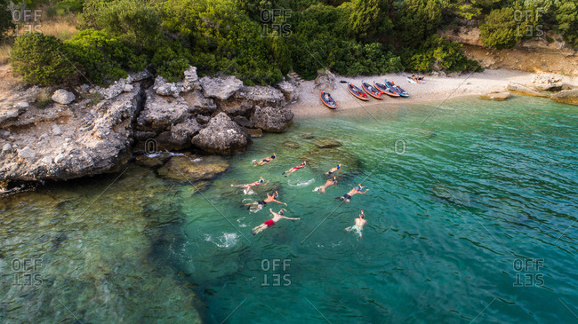 Aerial view of group of kayakers swimming at secluded beach near Drvenik in Dalmatia, Croatia.