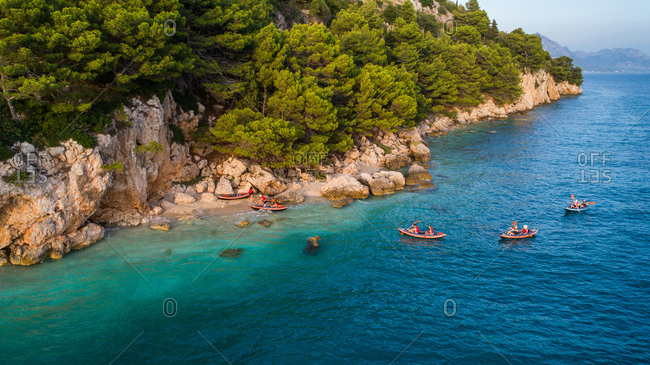 Aerial view of kayakers reaching a secluded beach near Zivogosce in Dalmatia, Croatia.