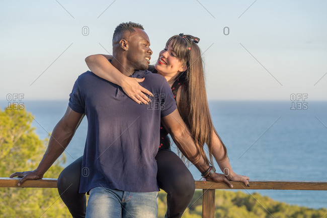 Happy multiethnic couple during date on terrace