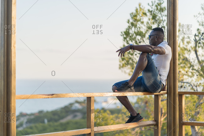 Side view of black man in casual clothes sitting on railing of gazebo and admiring sea in calm evening on resort