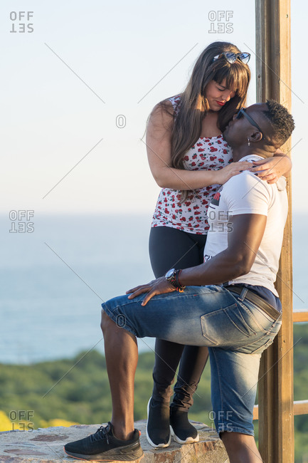 Cheerful woman smiling and hugging black boyfriend while sitting on railing against sea and sundown sky during romantic date in evening