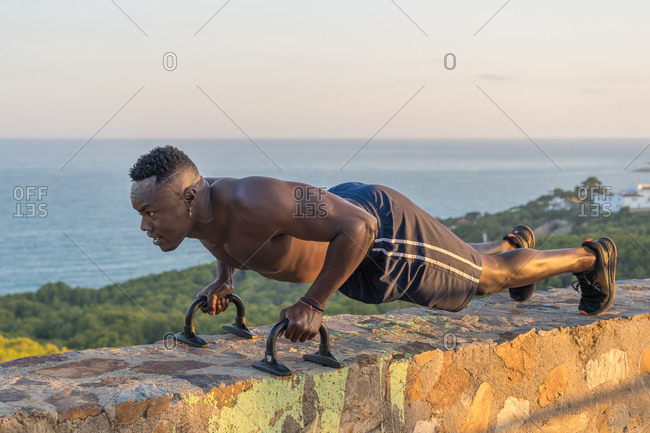 Black man exercising on border near sea