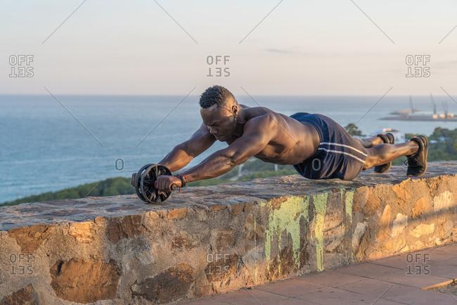 Shirtless African American guy doing abs exercise with wheel on rough border against calm sea and sunset sky during fitness training on embankment