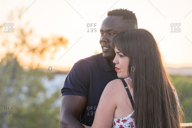 Cheerful woman smiling and hugging black boyfriend during romantic date in afternoon