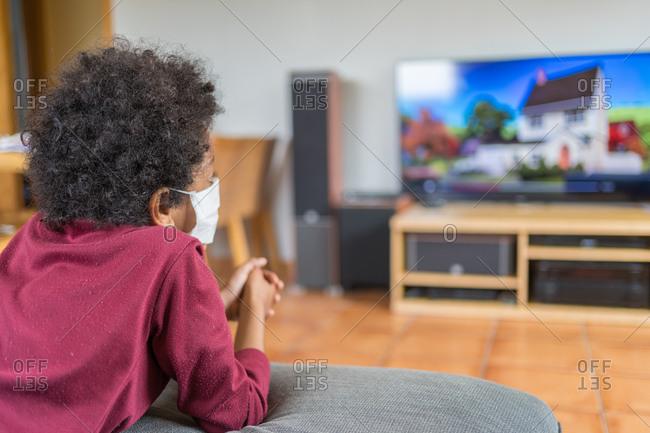 Black boy in medical mask watching TV at home during the coronavirus pandemic