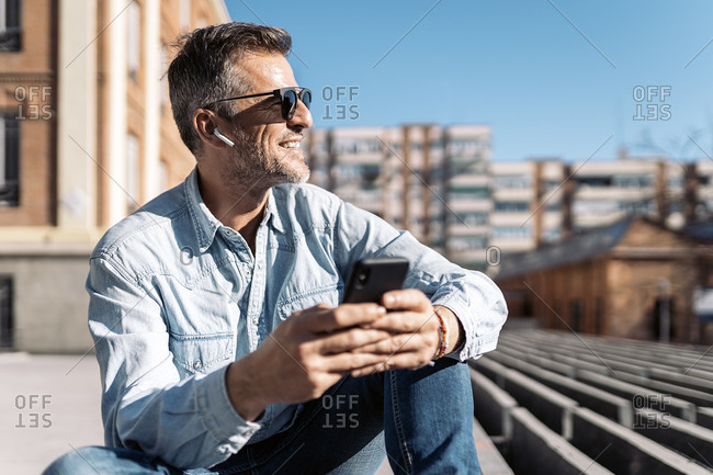 Stock photo of a business man seated in a bench in the street looking at a side and listening to music with his earphones. He is holding his smartphone with his two hands.