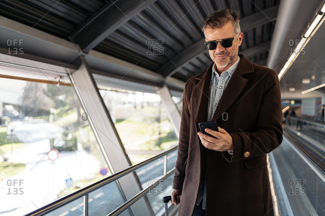 Stock photo of a caucasian business man checking his mobile phone before taking a flight at the airport. He is wearing casual clothes and sunglasses. He has a suitcase.