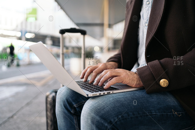 Stock photo of a side view close up of an unrecognizable business man typing in his laptop. He is seated on a bench. He has a suitcase near him.