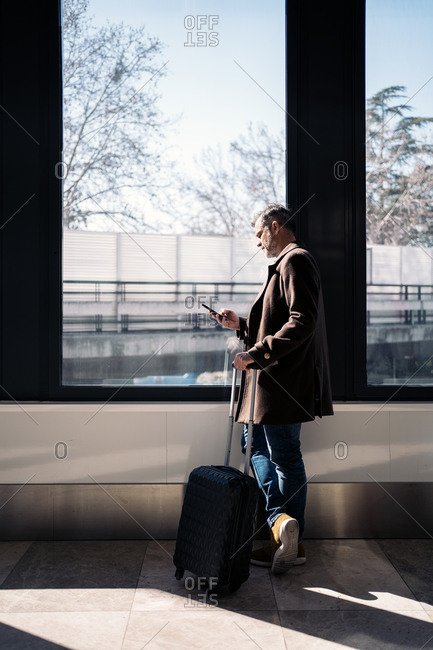 Stock photo of a caucasian business man using his phone in the airport. He is leaning on a window. He is smiling. He is wearing casual clothes.