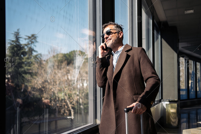 Stock photo of a caucasian business man talking on his phone in the airport. He is leaning on a window and looking trough it. He is smiling. He is wearing casual clothes and sunglasses.