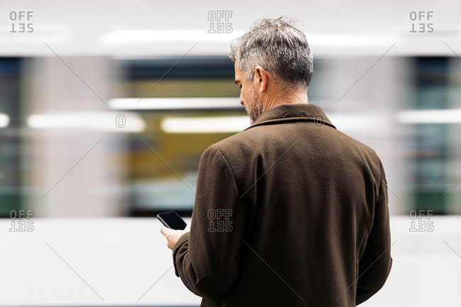 Stock photo of a business man typing in his smartphone waiting to take the underground in the platform. He is unrecognizable.