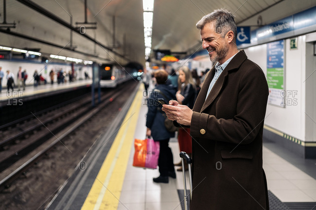 Stock photo of a side view of a business man typing in his smartphone waiting to take the underground in the platform. He is smiling and wearing casual clothes. There are people in the background.
