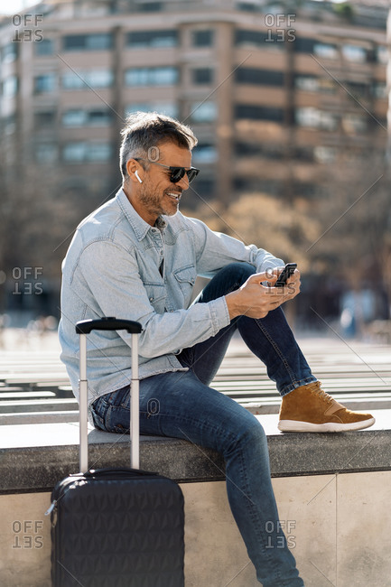 Stock photo of a business man seated in a bench in the street looking at his mobile phone and listening to music with his earphones. He is holding his smartphone with his two hands.