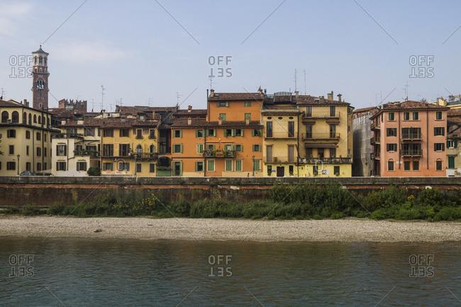 A view across the waters of the River Adige towards houses and the Torri di Lamberti in Verona, Italy