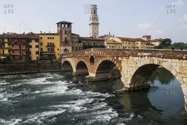 October 9, 2013: The ancient Ponte Pietra bride crossing the waters of the River Adige in Verona, Italy