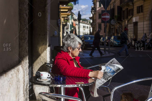 October 12, 2013: An elderly woman relaxes with a newspaper at a streetside cafe in Verona, Italy