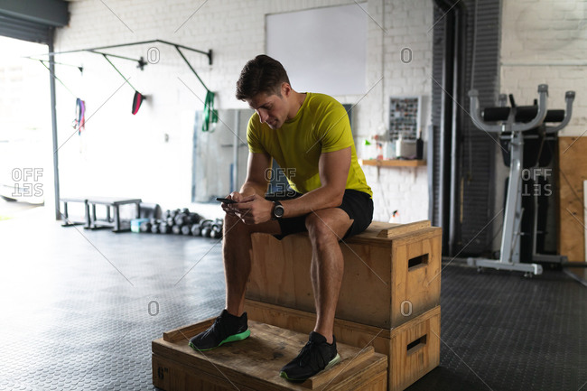 Front view of an athletic Caucasian man wearing sports clothes cross training at a gym, taking a break from training sitting on a box and using a smartphone