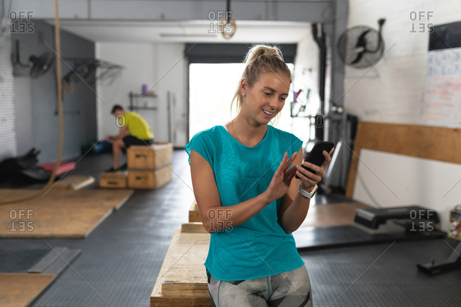 Front view of an athletic Caucasian woman wearing sports clothes cross training at a gym, taking a break from training leaning on a box, using a smartphone and smiling, with a male gym colleague sitting in the background