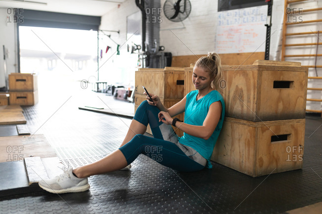 Side view of an athletic Caucasian woman wearing sports clothes cross training at a gym, taking a break from training sitting and leaning on a box, using a smartphone and smiling