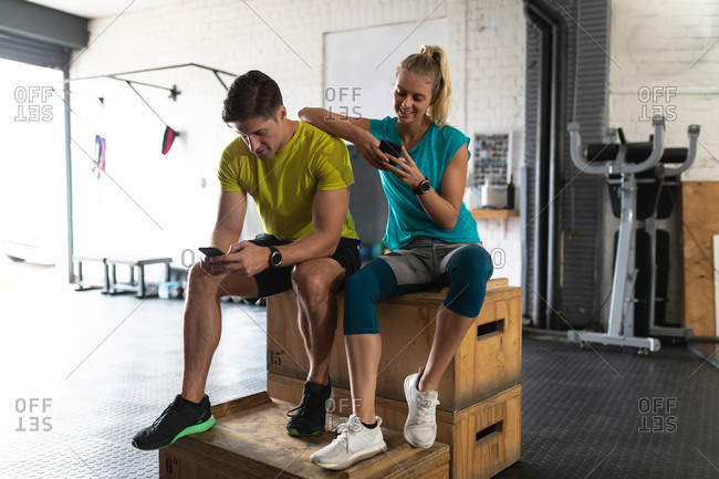 Front view of an athletic Caucasian man and woman wearing sports clothes cross training at a gym, taking a break from training sitting on a box and using their smartphones, the woman leaning on the man