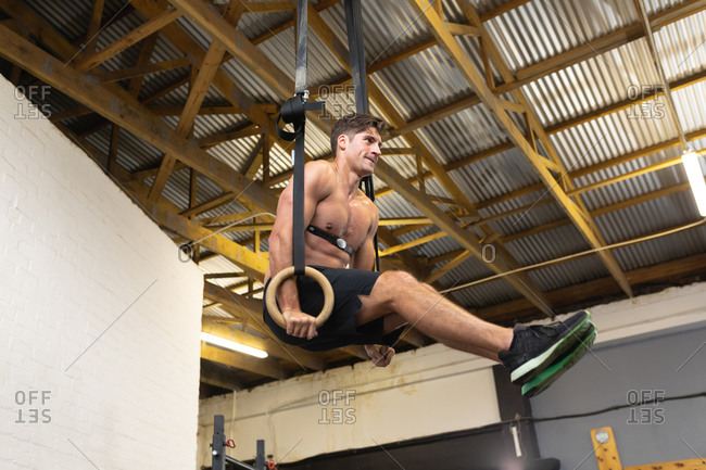 Side view of a shirtless athletic Caucasian man wearing a chest strap heart rate monitor cross training at a gym, lifting himself up on gymnastic rings with legs up