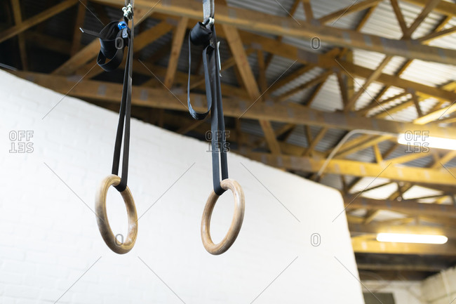 Low angle view of a pair of wooden gymnastic rings hanging on adjustable straps from wooden beams in the ceiling of a gym