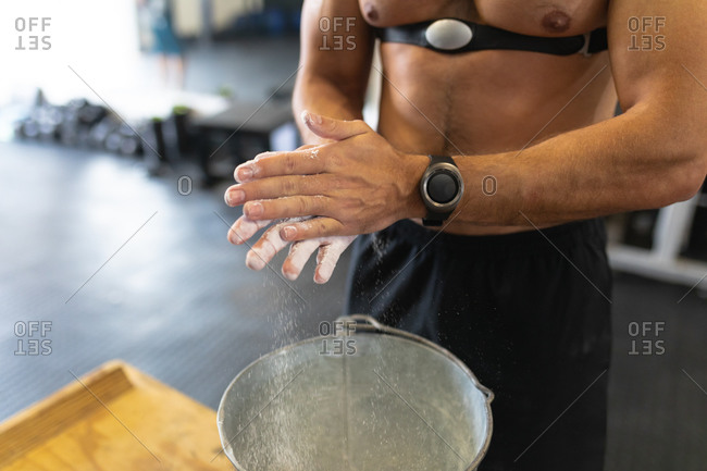 Front view mid section of a shirtless athletic Caucasian man wearing a chest strap heart rate monitor cross training at a gym, rubbing his hands with chalk in preparation for weight training