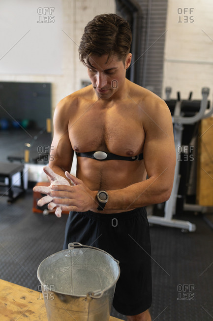 Front view of a shirtless athletic Caucasian man wearing a chest strap heart rate monitor cross training at a gym, rubbing his hands with chalk in preparation for weight training