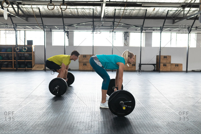 Side view of an athletic Caucasian man and woman wearing sports clothes cross training at a gym, weight training with barbells, standing and bending down to lift the weights from the floor
