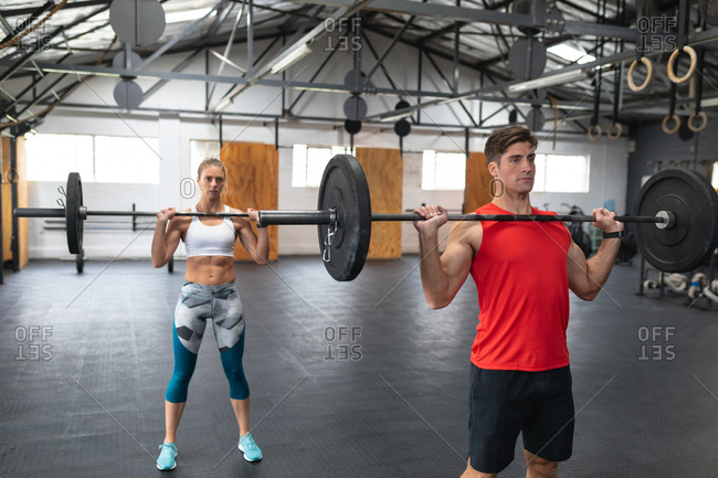 Front view of an athletic Caucasian man and woman wearing sports clothes cross training at a gym, standing and weight training with barbells, lifting them and holding them at chest level