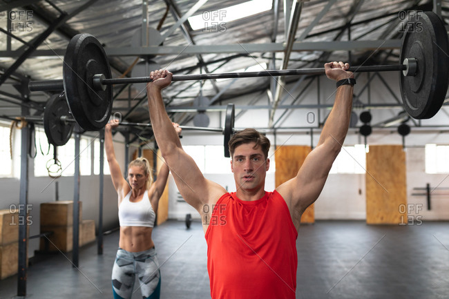 Front view of an athletic Caucasian man and woman wearing sports clothes cross training at a gym, standing and weight training with barbells, lifting the weights and holding them above their heads