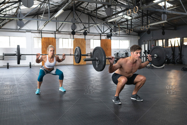 Side view of an athletic Caucasian man and woman wearing sports clothes cross training at a gym, weight training with barbells, squatting with the weights on their shoulders