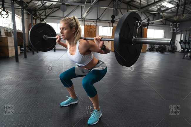 Side view of an athletic Caucasian woman wearing sports clothes cross training at a gym, weight training with barbells, squatting, lifting the weights on her shoulders