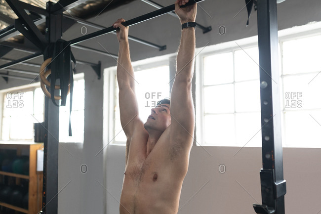 Side view of a shirtless, athletic Caucasian man cross training at a gym, hanging from a bar, doing pull ups