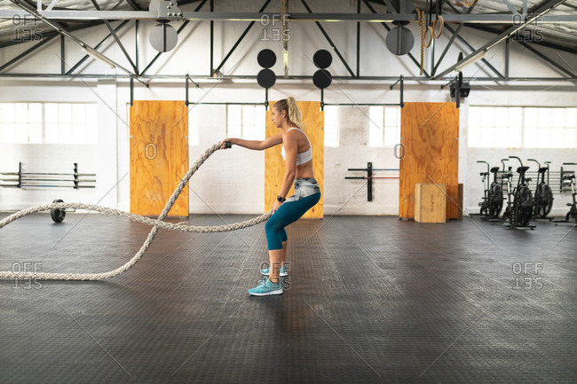 Side view of an athletic Caucasian woman wearing sports clothes cross training at a gym, working out with battle ropes, waving her arms with a rope in each hand