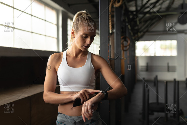 Front view of an athletic Caucasian woman wearing sports clothes cross training at a gym, standing and looking at smartwatch, using a fitness app