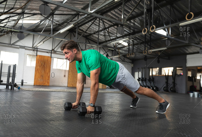 Side view of an athletic Caucasian man wearing sports clothes cross training at a gym, weight training with dumbbells, leaning in a press up position holding a dumbbell in each hand