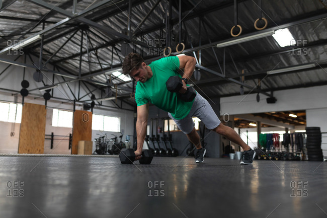 Front view of an athletic Caucasian man wearing sports clothes cross training at a gym, weight training with dumbbells, leaning on one arm holding a dumbbell, and lifting a dumbbell with the other