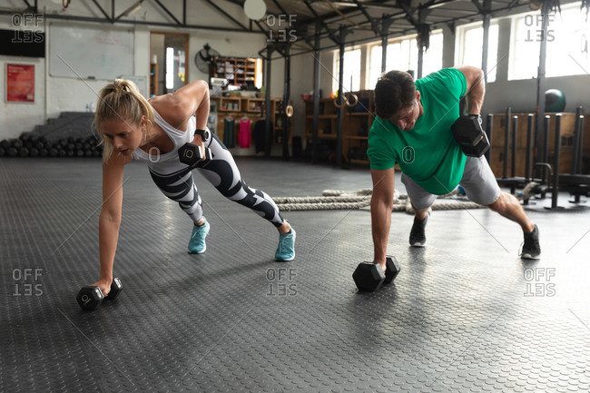 Front view of an athletic Caucasian man and woman wearing sports clothes cross training at a gym, weight training with dumbbells, leaning on one arm and lifting dumbbells with the other