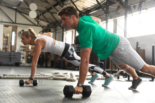 Side view close up of an athletic Caucasian man and woman wearing sports clothes cross training at a gym, weight training with dumbbells, leaning on one arm and lifting dumbbells with the other, looking straight ahead