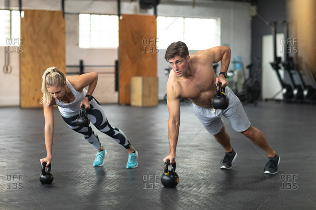 Front view of a shirtless athletic Caucasian man and woman wearing sports clothes cross training at a gym, weight training with kettlebells, leaning on one arm and lifting kettlebells with the other