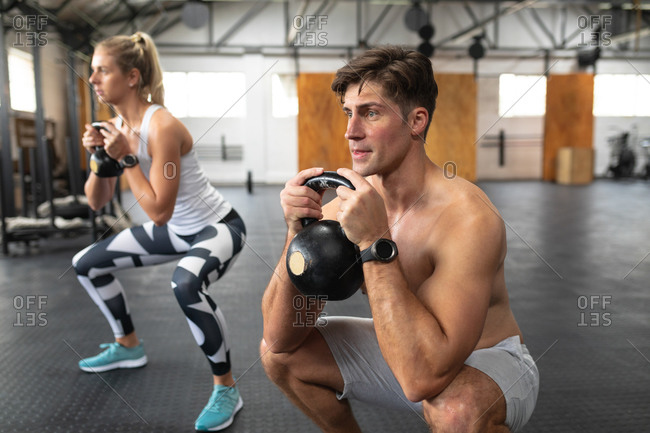 Front view of a shirtless athletic Caucasian man and woman wearing sports clothes cross training at a gym, weight training with kettlebells, squatting, holding the kettlebells in both hands and looking straight ahead