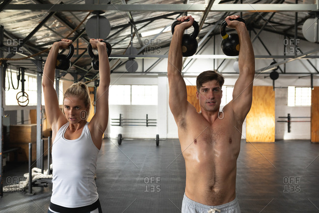 Front view of a shirtless athletic Caucasian man and woman wearing sports clothes cross training at a gym, weight training with kettlebells, standing, holding a kettlebell in each hand raised above their heads, and looking straight ahead