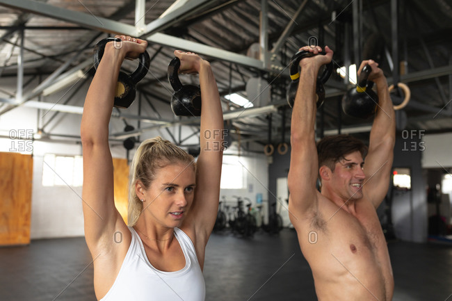 Side view close up of a shirtless athletic Caucasian man and woman wearing sports clothes cross training at a gym, weight training with kettlebells, standing, holding a kettlebell in each hand raised above their heads, looking straight ahead and smiling