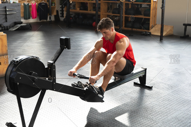 High angle front view of an athletic Caucasian man wearing sports clothes cross training at a gym, sitting with knees up, exercising on a rowing machine