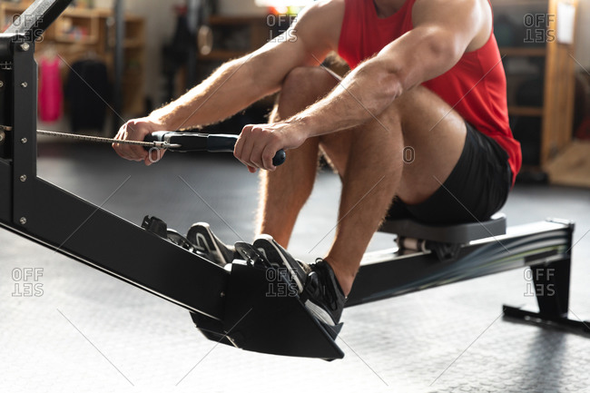 Front view mid section of an athletic Caucasian man wearing sports clothes cross training at a gym, sitting with knees up, exercising on a rowing machine