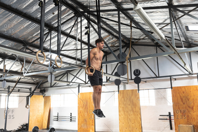 Side view of a shirtless athletic Caucasian man cross training at a gym, pushing himself up on gymnastic rings, lifting his body weight