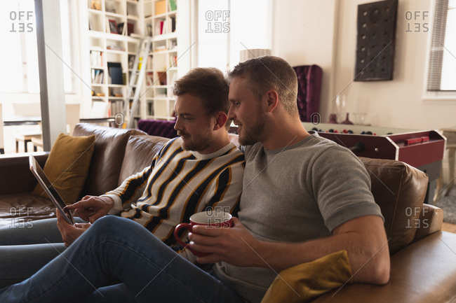 Side view of Caucasian male couple relaxing at home, sitting on a sofa, talking and smiling, holding cups of beverage while using a laptop together