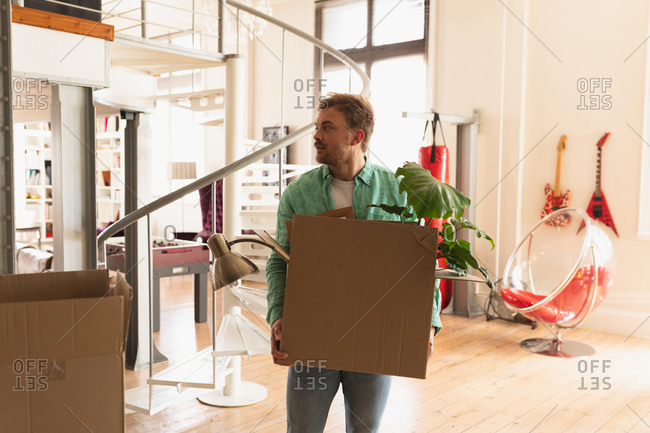 Front view of a young Caucasian man wearing green shirt, moving in to a new apartment, holding a cardboard box